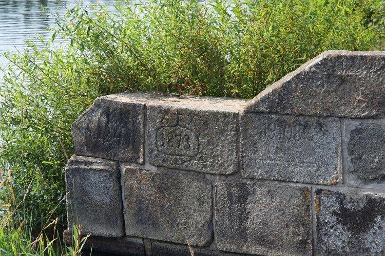 Přeliv Vysokopeckého rybníka s vytesanými letopočty rekonstrukcí