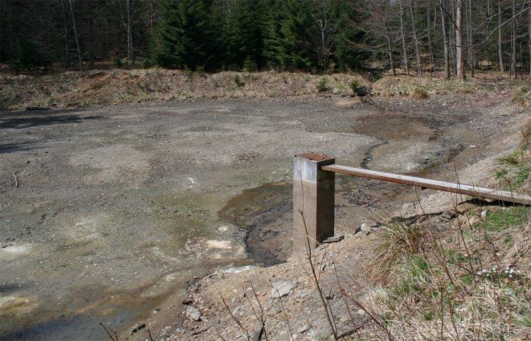 Na vypuštěném rybníčku je dobře viditelný uměle zbudovaný přítok